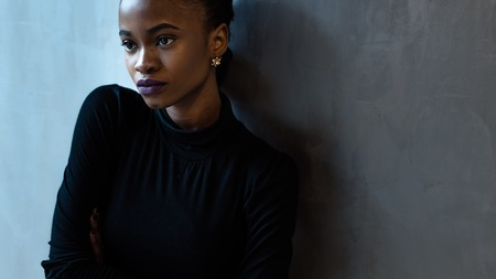Portrait of a serious african or black american woman with arms folded standing over gray background and looking away, close-up
