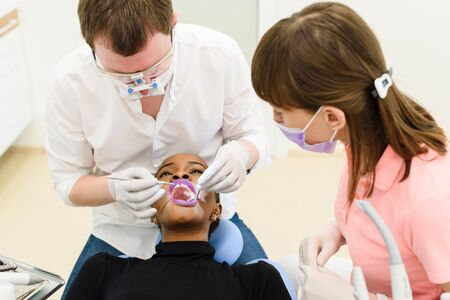 thorough: Dentist and his assistant carrying out a thorough examination. Stock Photo
