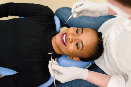 Young African-American ethnic black female smiling while dentist in white latex gloves check condition of her teeth. Banco de Imagens