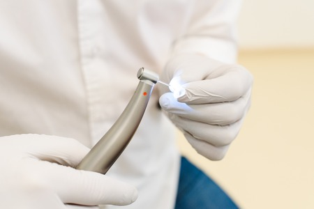 hand of dentist in white latex gloves holding dental drill machine