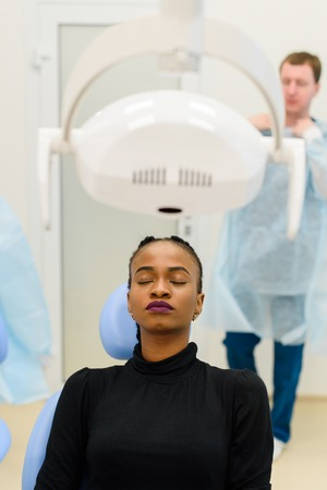 unease: African-American ethnic black patient sitting closing eyes waiting, while her dentist preparing to operation on background. Stock Photo