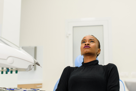 unease: Ethnic black female patient sitting looking up on dental chair waiting for her dentist.