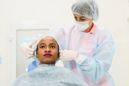 scrub cap: Dentist assistant putting scrub cap at female patient in the dental clinic. Stock Photo