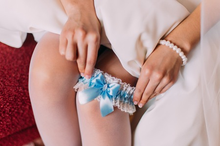 nudes: Young bride dresses garter on her leg, Picture of beautiful female legs in wedding dress.