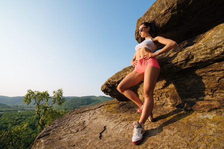 relying: Full length portrait of a young athletic female with perfect figure dressed in sportswear in mountain landscape. Healthy fit woman posing relying on the rock.
