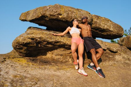 relying: Full-length fashion portrait of sexy fit mixed race couple with perfect bodies in sportswear relying on the rock. Mountains landscape. Sport and advertising concept.