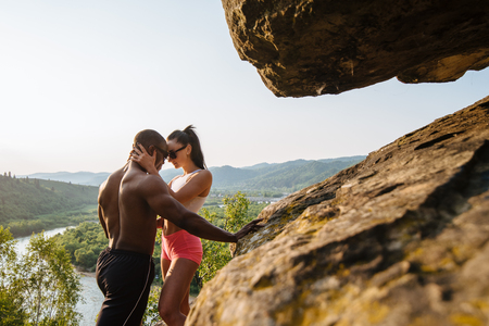 area sexy: Fit muscular mixed race couple african american man bodybuilder and sexy brunette woman in sportswear passionately embracing on the rocky mountains background. Stock Photo