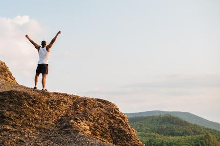 Czarny muskularny sportowiec na szczycie góry. Sport i koncepcja wolności.