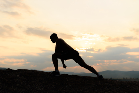 pres: Concept of beauty and sports. Silhouette of bodybuilder posing at sunset during his outdoor training.