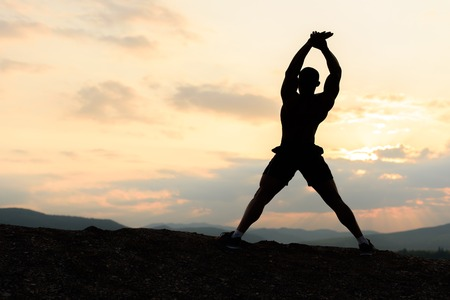 pres: Beauty of human body concept. African american bodybuilder posing at sunset during his outdoor training.