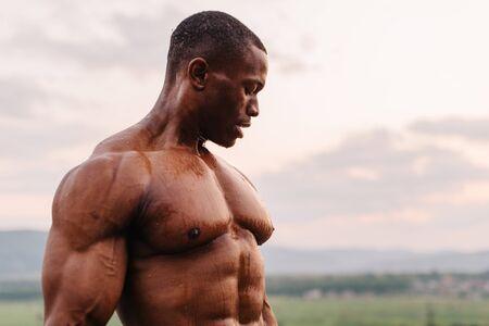 nipple man: Portrait of handsome black african american bodybuilder on the sunrise sky background. Stock Photo
