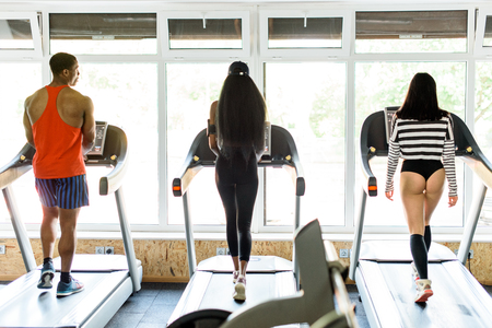 sexy asian girl: Healthclub. African-american man and woman with sexy asian girl walking on the treadmill on back view in gym
