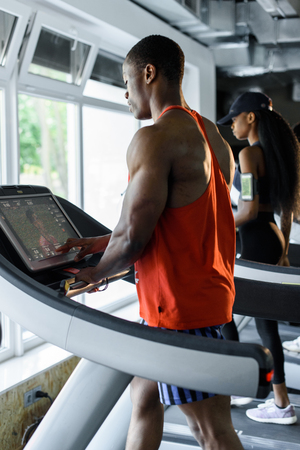 motivations: Muscular handsome black bodybuilder jogging on a treadmill in the gym.