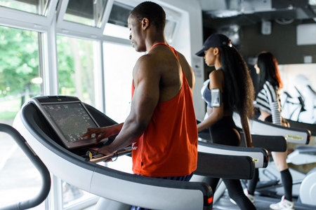 Back view of sporty black african-couple jogging on the treadmill in gym.