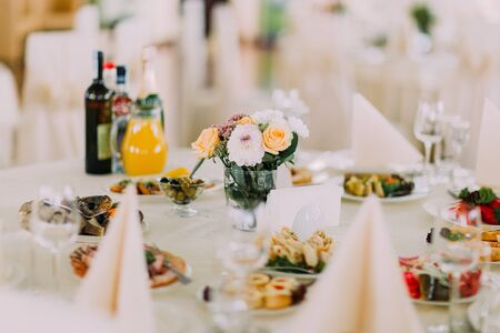 european food: Finely served banquet restaurant table with snacks, cutlery, wine, glasses and flower decoration. European food.