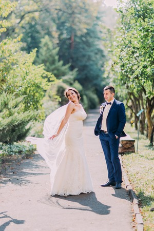 newly: Newly married couple posing in sunny park. Playful bride  showing her bridal veil.