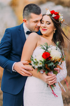 countryside loving: Loving groom kissing his pretty new wife on the cheek in the countryside. Light wind flapping womens hair under stylish head wreath.