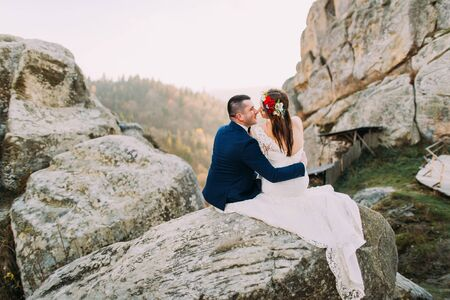 lovingly: Elegant groom in stylish blue suit lovingly holding white dressed bride with cute head wreath on majestic mountain rocky landscape as backround. Back view.