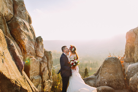 astonishing: Portrait of romantic newlywed couple kiss in sunset lights on astonishing mountain landscape with big rocks as background.