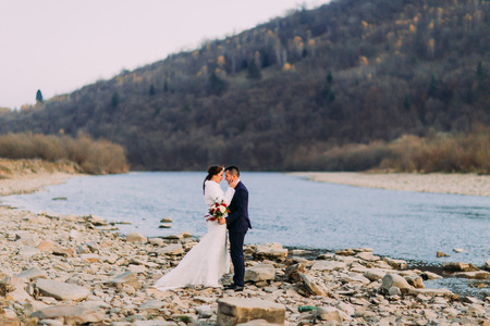 Romantic young bridal couple posing on pebble riverside with forest hills as background.