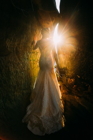 cleft: Silhouette of beautiful young woman wearing elegant white dress standing between two rocks with yellow sunset rays beaming through the cleft. Stock Photo