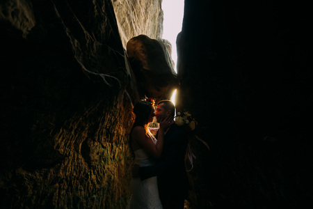 cleft: Romantic beautiful bride and elegant stylish groom kissing in darkened rock cleft backgrounded by sunset shining.