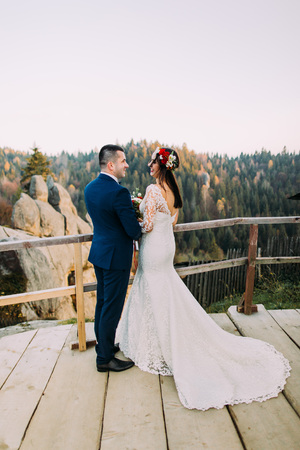 lovingly: Elegant groom in stylish blue suit lovingly holding his charming white dressed bride standing on wooden platform with majestic mountain rocky landscape as background. Back view. Stock Photo