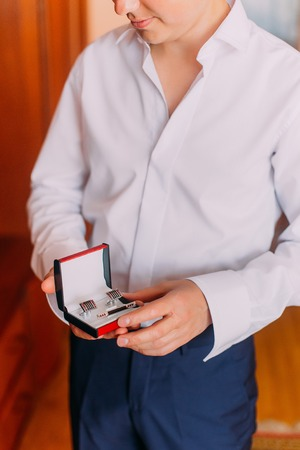 young  cuffs: Attractive young man holding stylish red black box with cufflinks and tie clip while dressing in. Stock Photo