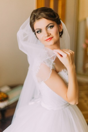 bridal gown: Beautiful bride in white wedding dress posing with veil. Female portrait in bridal gown for marriage.