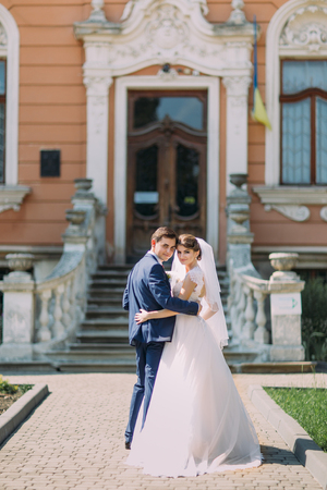 newly married couple: Romantic newly married couple charming bride and stylish groom posing in front of antique building entrance. Stock Photo