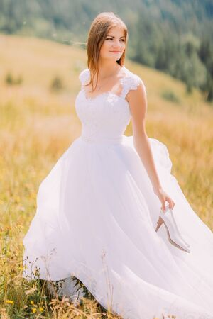 loose hair: Bride with loose hair posing on the golden autumn field. Mountain forest landscape behind her. Stock Photo