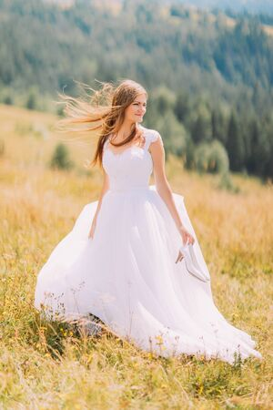 astonishing: Beautiful bride posing on the golden autumn field with astonishing mountain landscape behind her.