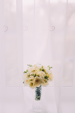 cut glass: Beautiful bouquet of flowers in cut glass vase on windowsill. Bright window with white curtains at background.
