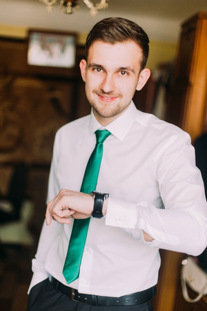 french cuffs: Young handsome businessman in white shirt with green tie checking time looking on his watch.