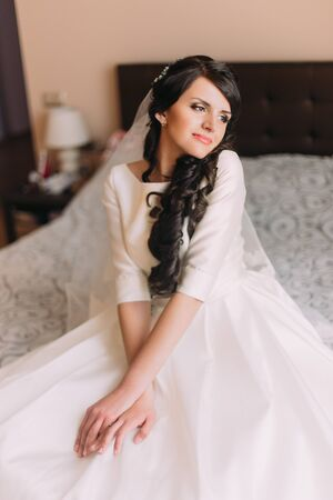 exalted: Young fashionable excited bride sitting on bed in wedding dress and dreaming of her new married life.
