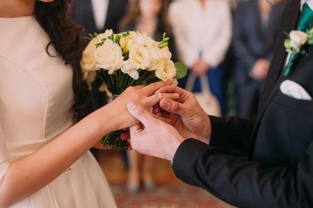 Stylish groom putting ring on finger of his elegant bride at wedding ceremony.