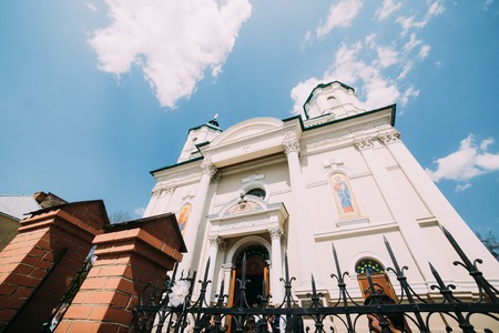 eastern european: Low angle view of eastern european church with pointy fence under blue sky.