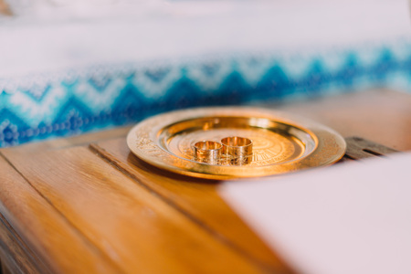 slavic: Pair of wedding rings on a golden salver with traditional slavic ornamented cloth at background. Stock Photo
