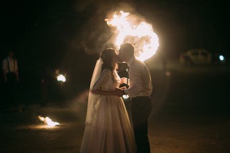 hands fire passion: Romantic newlyweds kissing at night in front of flaming heart.