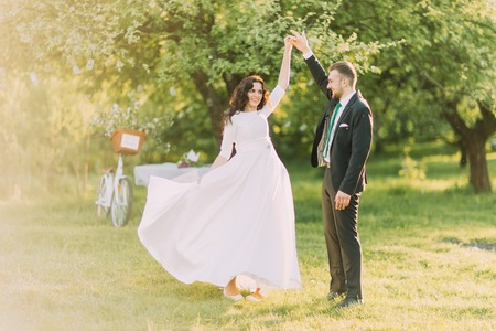 flatter: Happy just married couple dancing on lawn in green sunny park. Brides dress flatter while she moves.