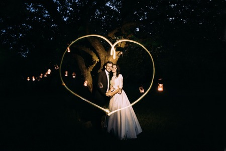 under heart: Beautiful bride and groom in evening park holding each other under tree decorated with many lanterns. Lightpainted heart. Stock Photo