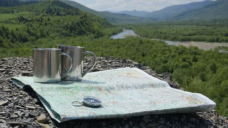 travel mug: Travel accessories to the adventure in mountains: mug, conpass and map on the green nature background.