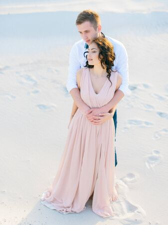 softly: Portrait of happy sensual young lovers softly embracing on the sand in desert. Stock Photo