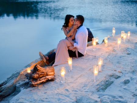 Knappe man en sensuele brunette vrouw aan het meer strand omgeven door veel kaarslichten tegen de zonsondergang. Romantisch liefdesverhaal. Stockfoto