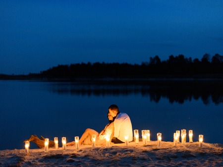 Beautiful young couple in love at the lake surrounded by many burning candles. Evening time.