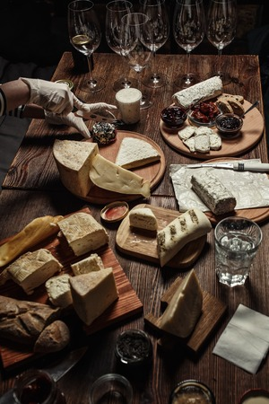 different types of cheese: Various types of cheese with different spices and wine glasses on the empty space background.