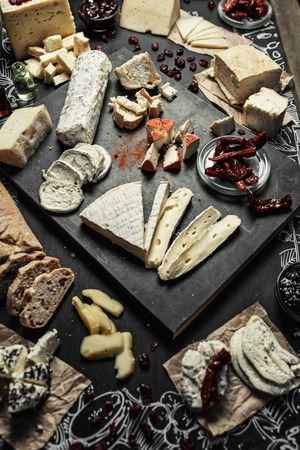 different types of cheese: Various types of cheese with different spices, wine glasses and bread slices on the empty space background.
