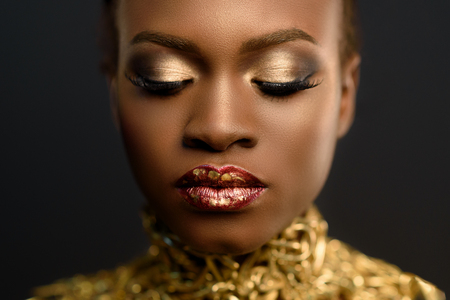 bodypaint: Fashion Portrait of Glossy African American Woman with Bright Golden Makeup. Bronze Bodypaint, Black Studio Background.