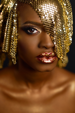 High fashion portrait of young african american female model with gold glossy makeup and hairstyle. Face art
