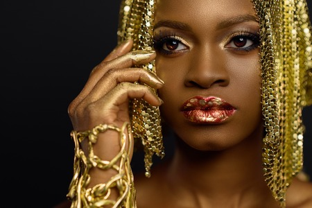 Sexy african american female model with glossy makeup and golden wig. Face art